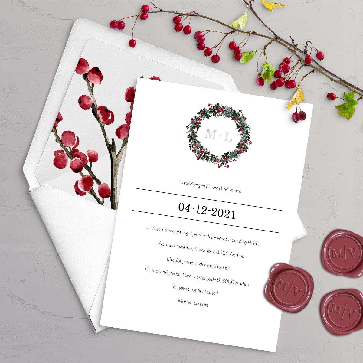 Bryllupsinvitationen Winter Wreath med monogram i sølvfolie. Et smukt design til et vinterbryllup med krans i gran, kristtjørn og grene med røde bær.