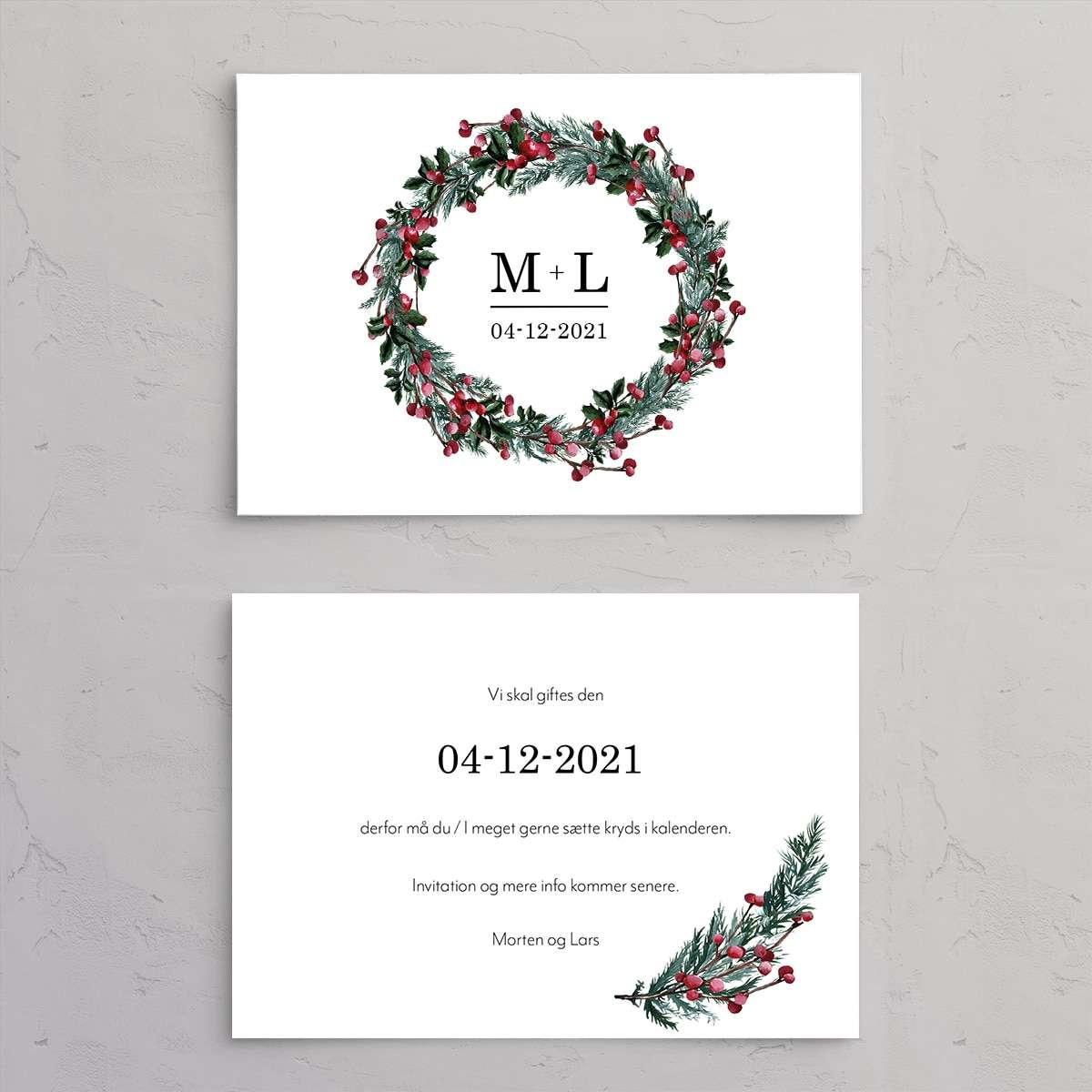 Save the date kort med trykt tekst på bagsiden til bryllupsinvitationen Winter Wreath med monogram. Et smukt design til et vinterbryllup med krans i gran, kristtjørn og grene med røde bær.