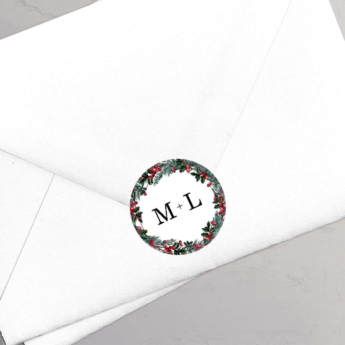 Klistermærke med monogram til bryllupsinvitationen Winter Wreath. Et smukt design til et vinterbryllup med krans i gran, kristtjørn og grene med røde bær.