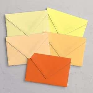 C5 kuvert i gule og orange nuancer med spidsklap i farvene Daffodil (pastelgul), Limoncello (citrongul), Buttercup (pastelorange), Marigold (lys orange) og Orange.