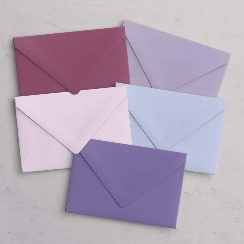 C5 kuverter i lilla nuancer til A5 invitationer med spidsklap i farvene Heather (lyng / rødlilla), Lilac (Syren / lys lilla), Periwinkle (lys blålilla), Petal (lyserød / lys pink / sart rosa), Lavender (lilla / lavendel)