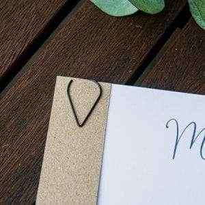 Dråbeformet papirclips i sort metal. Perfekt til at fastsætte bordkort med menukortet eller til kæreskilt på invitationen.