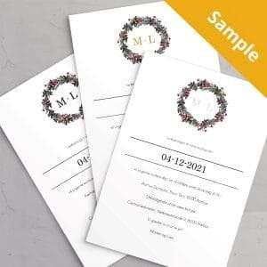 Sample af Bryllupsinvitationen Winter Wreath med monogram i sort / sølvfolie / guldfolie. Et smukt design til et vinterbryllup med krans i gran, kristtjørn og grene med røde bær.